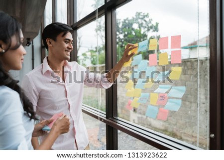business teamwork in meeting collecting some idea and stick it on the glass window #1313923622
