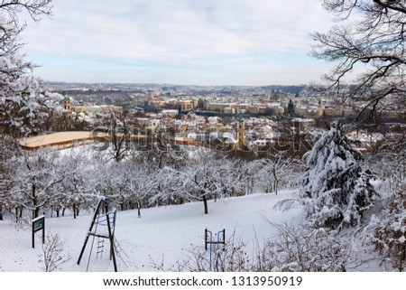 Snowy Prague City with St. Nicholas' Cathedral from Hill Petrin in the sunny Day, Czech republic #1313950919