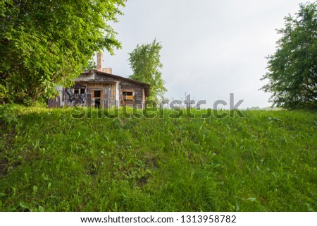 Old abandoned wooden house with a flowing wooden roof. Green vegetation and hills around #1313958782