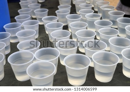 Disposable plastic water cups on table for drinking at a road race. Plastic recycling #1314006599