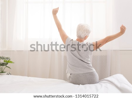 Senior woman sitting on her bed in morning, stretching with arms raised, back view, free space #1314015722