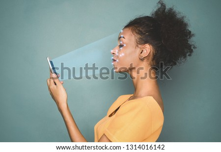 Biometric identification. African-american woman scanning face with facial recognition system on smartphone #1314016142