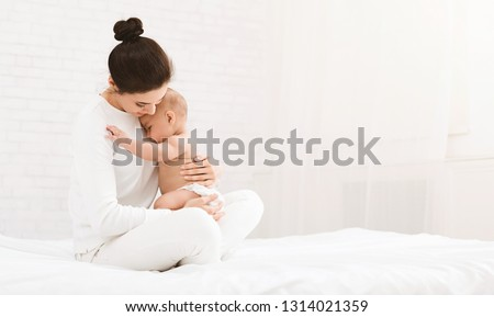 Young mother holding her newborn child, lulling baby in bed, copy space Royalty-Free Stock Photo #1314021359