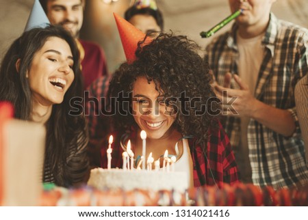 Excited girl ready to blow out candles on cake on birthday party with happy friends. Happy birthday dear friend concept