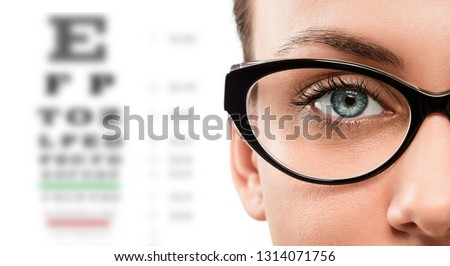 Cloese up of young woman wearing eyeglasses with eye test in the background Royalty-Free Stock Photo #1314071756