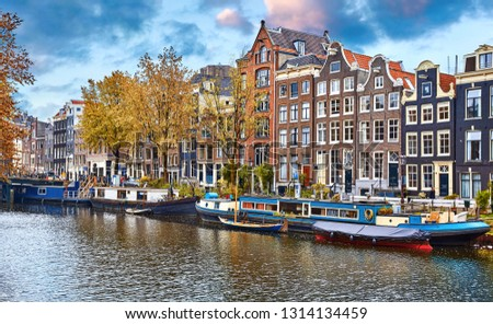 Amsterdam, Netherlands. Floating Houses, houseboats and boats at channels by banks. Traditional dutch dancing houses among trees. Evening autumn street above water blue sky with clouds. #1314134459
