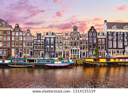 Amsterdam, Netherlands. Floating Houses and houseboats and boats at channels by banks. Traditional dutch dancing houses among trees. Evening autumn street above water pink sunset sky with clouds. #1314135539