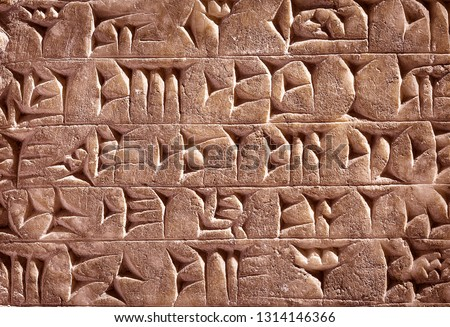 Ancient cuneiform from Babylon in Mesopotamia. Assyrian and Sumerian writing carved on clay or stone. Remains of the culture of ancient civilization in the Middle East. Old cuneiform script close-up. #1314146366