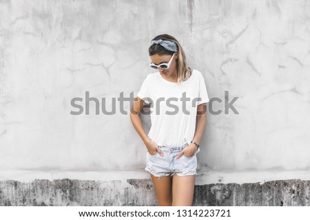 Hipster girl wearing blank white t-shirt and denim shorts posing against gray street wall, blank mockup for tshirt print store #1314223721