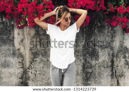 Hipster girl wearing blank white t-shirt posing against gray street wall with spring flowers, blank mockup for tshirt print store #1314223739