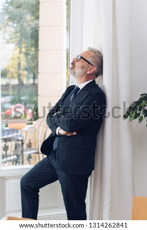 Bearded mature man in business suit and glasses, standing at glass door with his arms crossed, looking up and thinking, leaning back on the wall. Indoor side portrait with sunny day outside #1314262841