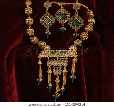Designer Golden pendent neck set closeup macro image on red background.  #1314294314