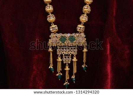 Designer Golden pendent neck set closeup macro image on red background.  #1314294320