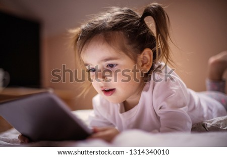 Technology addict. Little girl using digital tablet in bed. Close up. #1314340010