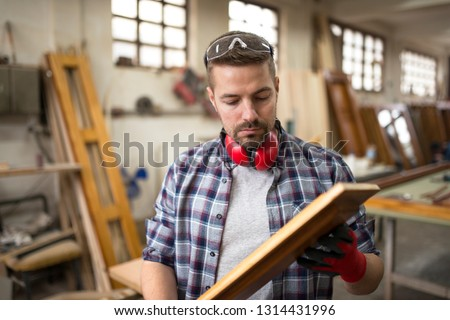 Focused professional worker carpenter checking quality of wood product in carpentry workshop. #1314431996