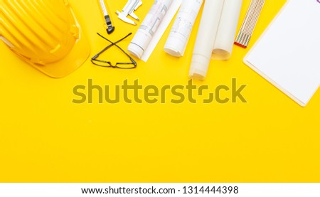 Architect engineer workplace, construction site desk. Project blueprints, hard hat and engineering tools on yellow, top view, copy space #1314444398