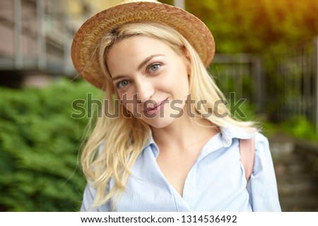 Young student blonde in a straw hat and a pink backpack is standing on the front of the university. Back to school concept #1314536492