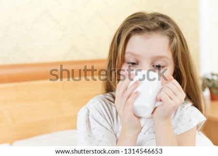 little girl on the bed with a cup in her hands, the child caught a cold and drinks tea in bed #1314546653