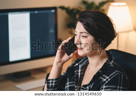 pretty young woman having a business call in a home office #1314549650