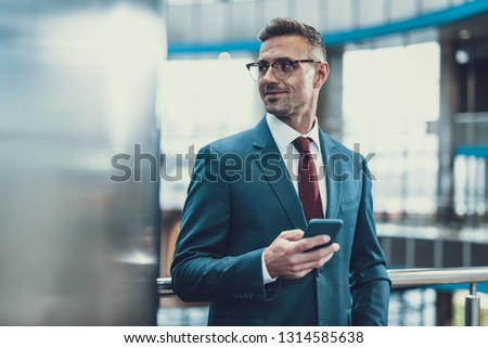 Attractive, good-wearing adult man in suit standing inside business center. He looking aside, smiling and holding telephone in hand #1314585638