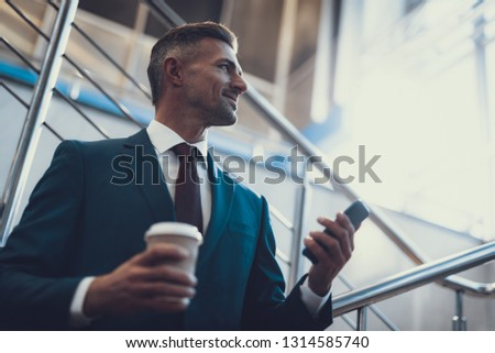 Low angle view photo of elegant adult man in suit. He holding brown cup of beverage and cellular phone in hands #1314585740