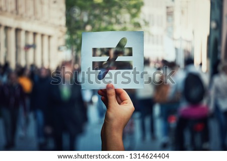 Human inequality as global social issue. Stop discrimination on grounds of race, sex or religion as hand holding a paper sheet with injustice, unfairness symbol over crowded street background. #1314624404