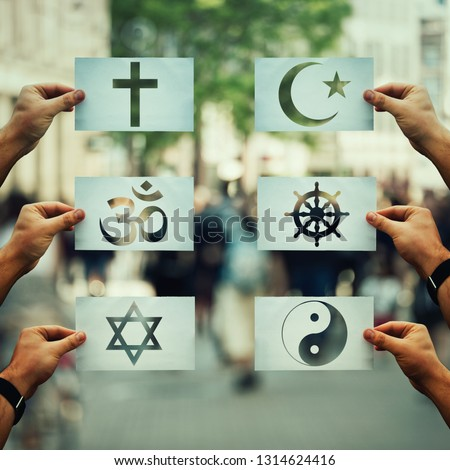 Religion conflicts as global issue concept. Human hands holding different paper with faith symbols over crowded street scene. Relations between different people doctrines and beliefs, social problem. Royalty-Free Stock Photo #1314624416