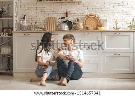 Young couple on the kitchen. Man and woman cooking. Boyfriend and girlfriend indoors on the kitchen. #1314657341