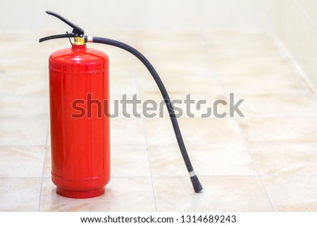 Fire extinguisher bright red isolated on white light tiles walls and floor copy space background. Danger and safety, fire protection concept. #1314689243