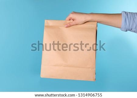 Woman holding paper bag on color background. Mockup for design #1314906755