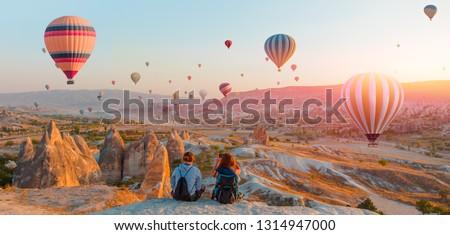 Hot air balloon flying over spectacular Cappadocia - Girls watching hot air balloon at the hill of Cappadocia #1314947000