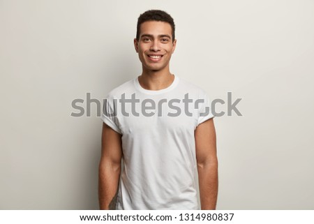 Optimistic youngster with toothy smile, dark eyes and short hairstyle, wears casual t shirt, has tattoo on arm, looks at camera with happiness, isolated over white studio background, enjoys great day #1314980837