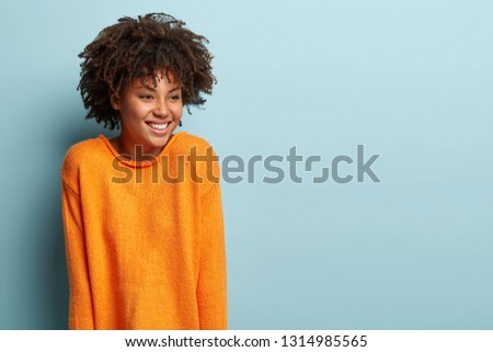 Optimistic glad dark skinned lady with curly hair, smiles broadly, shows white teeth, has dreamy happy expression, wears orange sweater, models over blue background with empty space for slogan #1314985565