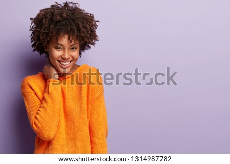 Upbeat tender young girlfriend with curly hairstyle, keeps hand on neck, wears bright outfit, smiles broadly, shows white teeth, models over purple background with empty space for your promotion #1314987782