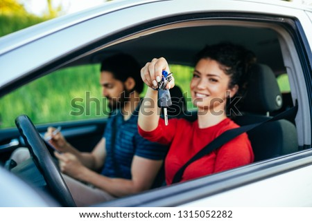 Driving school. Beautiful young woman successfully passed driving school test. She is sitting in car, looking at camera and holding car keys in hand. #1315052282