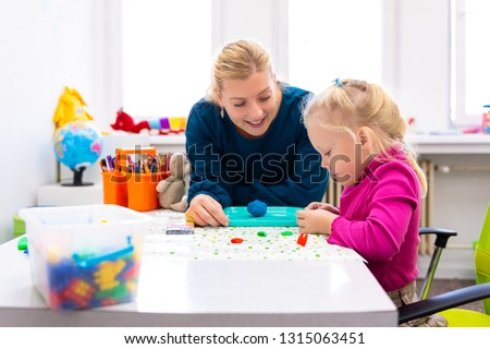 Toddler girl in child occupational therapy session doing sensory playful exercises with her therapist.  #1315063451