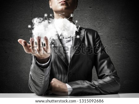 Businessman in suit keeping cloud with network connections in hand with gray wall on background. #1315092686