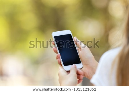Woman holding and using smartphone on blurred background #1315121852