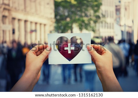 Health and wellbeing global issue as human hands holding a paper sheet with heart and cross icon over a crowded street background. Healthcare medical insurance, good life concept. Royalty-Free Stock Photo #1315162130