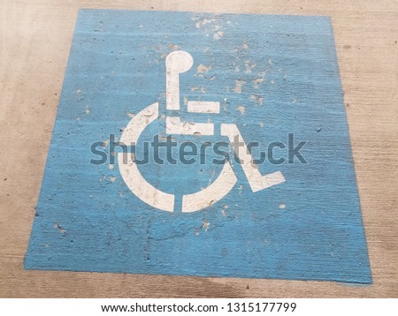 blue wheelchair or handicapped parking symbol on cement #1315177799