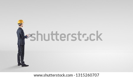 Young architect with construction helmet standing in an empty space and holding a plan #1315260707