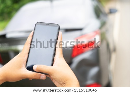 Man Hand Taking Photo Of Car Accident Through Smartphone, close up.Insurance agent using smart phone to take a photo photographing vehicle of damage car crash.