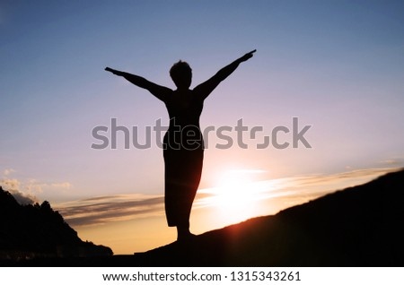 Silhouette of a mature woman with her arms spread out to the side, like wings, against the sunset sky #1315343261