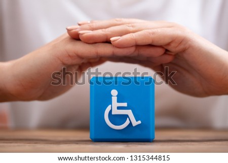 Close-up Of A Woman's Hand Protecting Blue Cubic Block With Disabled Icon #1315344815