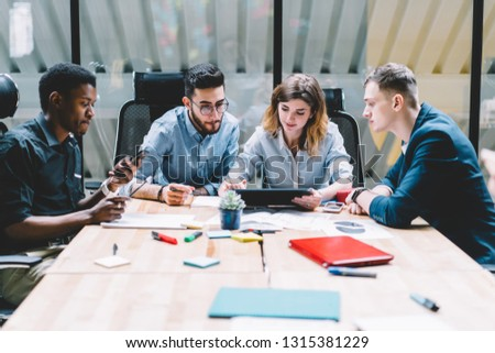 Group of caucasian creative workers discussing project ideas and researching business solutions while sitting at office table during meeting. four young employees brainstorming and sharing opinions #1315381229