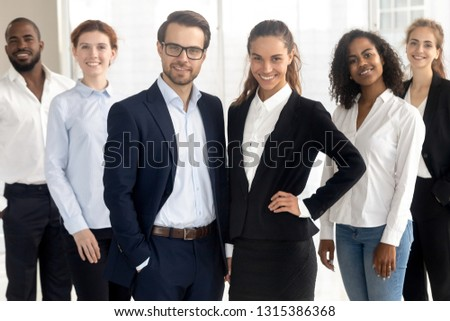 Smiling different ethnicity diverse professionals company members wearing formal clothes posing together looking at camera standing in modern office. Successful team portrait, motivated staff concept #1315386368