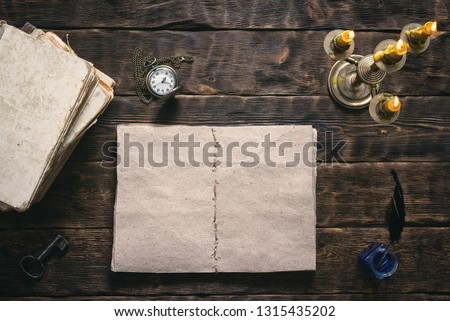 Open blank page book, old literature, pocket watch and a inkwell with quill pen on a writer wooden table background. #1315435202