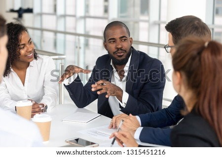 Millennial employees gathered in boardroom for training, black boss ceo leader leading corporate team during seminar learning at modern office. Internship and leadership coaching and education concept Royalty-Free Stock Photo #1315451216