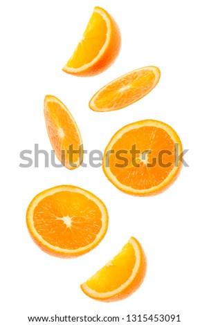 falling fresh orange fruit slices isolated on white background closeup. Flying food concept. #1315453091
