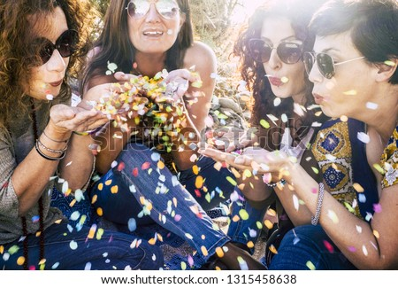 Group of attractive middle age young women playing and blowing out a lot of coloured confetti in the air - celebrate and having fun together with friendship - party outdoor concept with sun backlight #1315458638